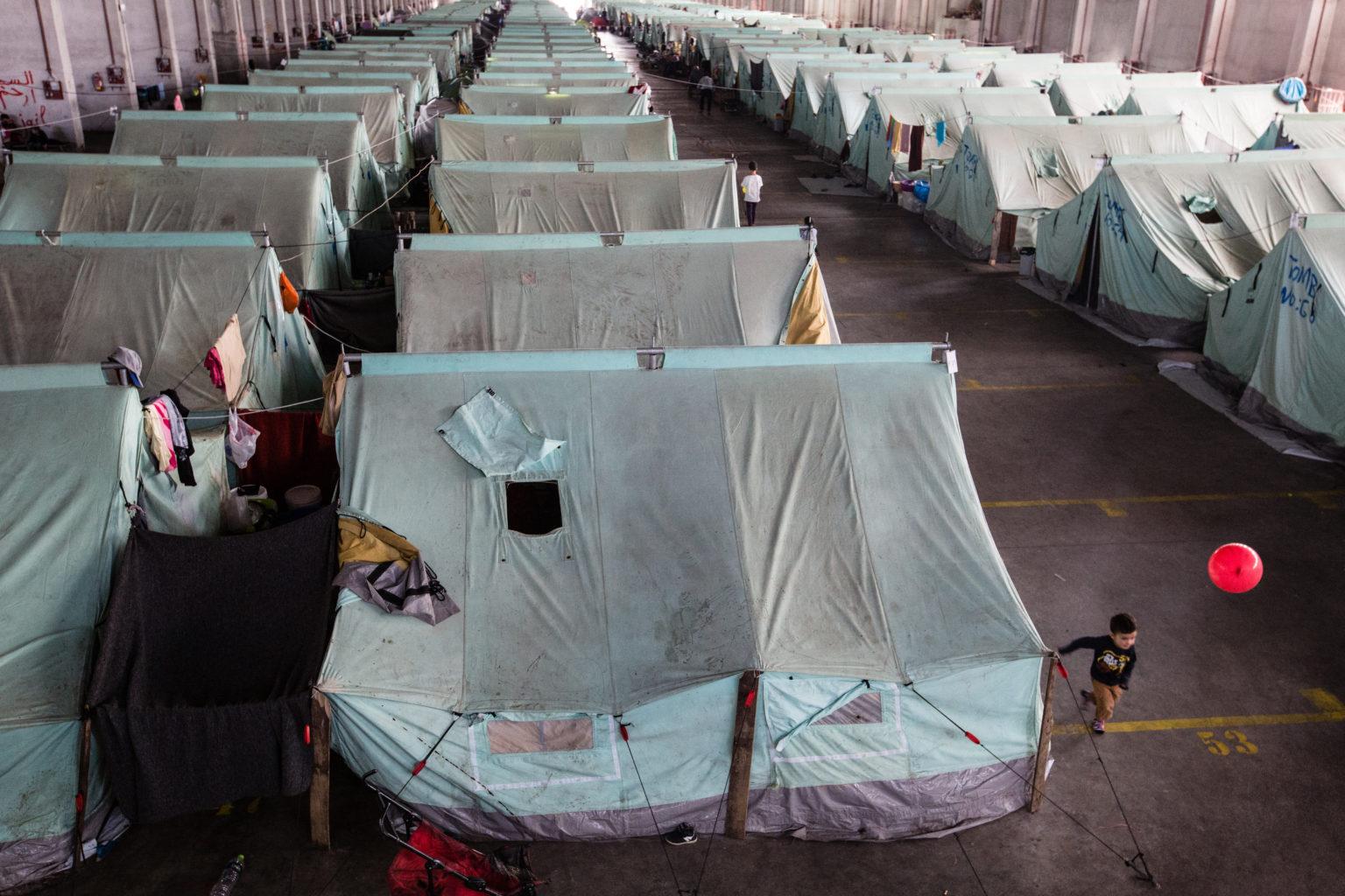 Griekenland, vluchtelingen, 2016, noorden Griekenland, Oreokastro, dichtbij Thessaloniki, oude hangar van fabriek, die nu dienst doet als officiëel vluchtelingenkamp, 1157 refugees live here, mainly Syrians, Iraqis and Kurds